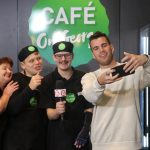 Four people pose together for a selfie in front of the Cafe on George logo. Photo has been taken after the Studio 10 interview finsihes