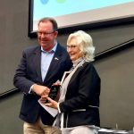 Stuart Coward shakes hands with Linda Ritchie as she accepts her award and smiles for the camera