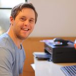 Young-man-sitting-at-desk-smiling