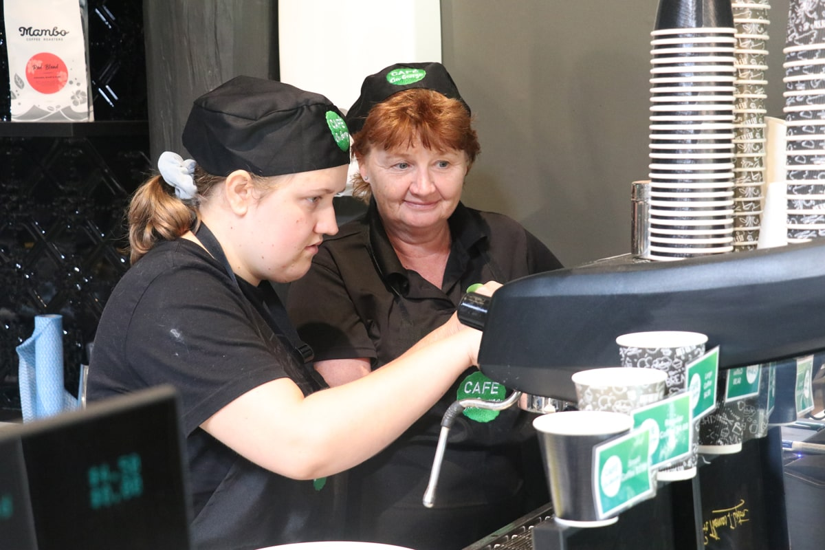 STEPS Pathways College student being taught how to use the coffee machine at Café on George