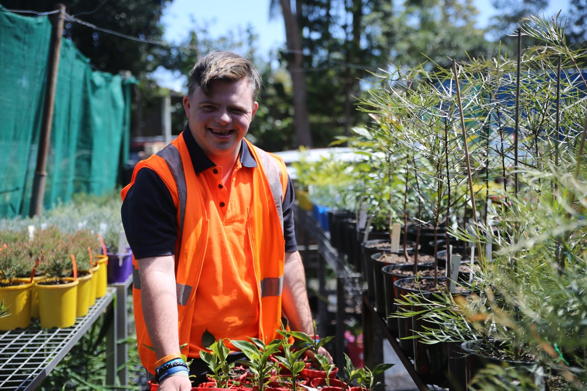 Male standing holding a tray of plants at the STEPS Nursery